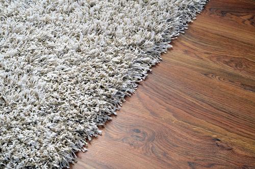 White shaggy carpet on brown wooden floor